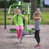 Маленькие милые девушки делая тренировки на общественном спортивном инвентаре Спорт Стоковые Фотографии RF