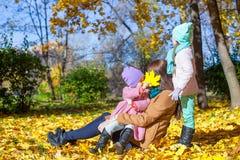 Маленькие милые девушки и молодая мать в осени паркуют Стоковая Фотография