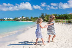 Маленькие милые девушки идя вдоль белого пляжа Стоковая Фотография
