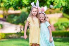 Маленькие милые девушки с ушами зайчика на празднике пасхи Стоковые Изображения