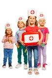 Маленькие доктора при медицинская коробка давая скорую помощь Стоковое Изображение RF