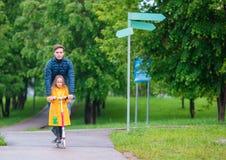 Маленькие прелестные девушки ехать на самокатах с папой в парке осени outdoors Стоковые Фото