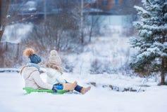 Маленькие прелестные девушки наслаждаются ездой саней Ребенок Стоковое Изображение RF