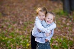 Маленькие прелестные девушки на теплом дне в осени паркуют Стоковое фото RF