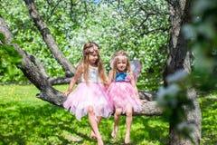 Маленькие прелестные девушки сидя на blossoming дереве Стоковое Фото