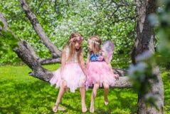 Маленькие прелестные девушки сидя на blossoming дереве Стоковое Изображение RF