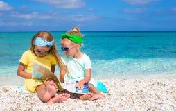 Маленькие прелестные девушки с большой картой на тропическом Стоковые Фотографии RF