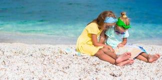 Маленькие прелестные девушки с большой картой на тропическом Стоковая Фотография RF