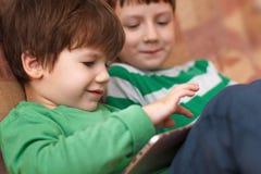 Маленькие ребеята играя на таблетке стоковые фотографии rf