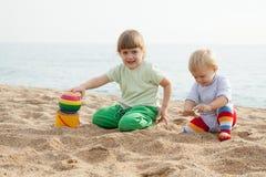 Маленькие ребеята сидя на пляже Стоковые Изображения RF