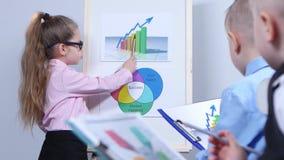 Маленькие ребеята учтены диаграммами в руках мальчиков с папкой документов сток-видео