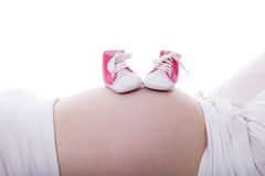 Маленькие розовые ботинки на беременном животе стоковые изображения rf