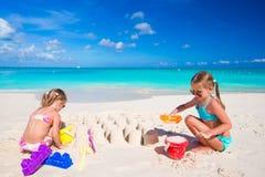 Маленькие сестры играя с игрушками пляжа во время Стоковые Фото