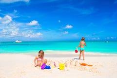 Маленькие сестры играя с игрушками пляжа во время Стоковая Фотография