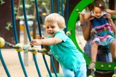 Маленькие сестры на спортивной площадке в парке Стоковое Изображение RF