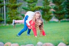 Маленькие счастливые девушки имеют много потеху outdoors в парке Стоковое Изображение