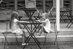Маленькие счастливые девушки имеют потеху на внешнем кафе Стоковое Изображение