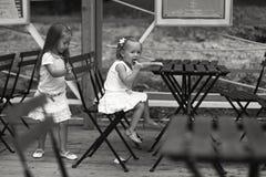 Маленькие счастливые девушки имеют потеху на внешнем кафе Стоковое Фото