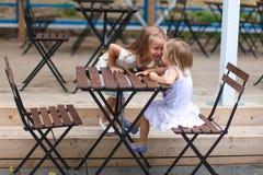 Маленькие счастливые девушки имеют потеху на внешнем кафе Стоковые Изображения RF