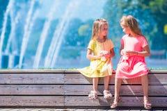 Маленькие счастливые девушки имеют потеху около фонтана улицы Стоковое Фото
