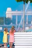 Маленькие счастливые девушки имеют потеху около фонтана улицы Стоковое Изображение RF