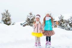 Маленькие счастливые девушки катаясь на коньках outdoors в снеге зимы Стоковое фото RF