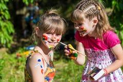 Маленькие счастливые сестры играют с цветами в парке, игре детей, одине другого краски детей Стоковые Изображения RF