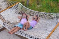 Маленькие сладостные девушки ослабляя в гамаке на лете Стоковые Изображения
