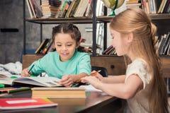 Маленькие школьницы сидя на таблице и делая домашнюю работу совместно Стоковое Фото