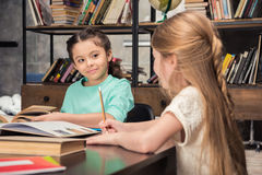Маленькие школьницы сидя на таблице и смотря один другого Стоковая Фотография