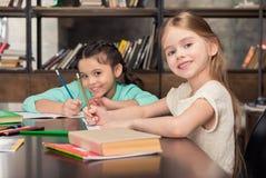 Маленькие школьницы сидя на таблице с книгами и усмехаясь на камере Стоковая Фотография