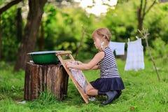 Маленькие girlwashes хелпера одевают используя washboard outdoors Стоковые Изображения RF