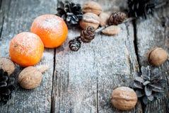 Маленькие Tangerines, конусы сосны, грецкие орехи, карточка праздника, селективная Стоковое Изображение