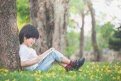 Маленький азиатский мальчик сидя под деревом и рисуя в тетради стоковое изображение rf