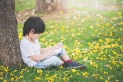 Маленький азиатский мальчик сидя под деревом и рисуя в тетради стоковое фото
