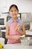 Маленький азиатский милый шеф-повар варя хлебопекарню в кухне Стоковое Фото