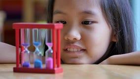 Маленький азиатский ребенок смотря часы сток-видео