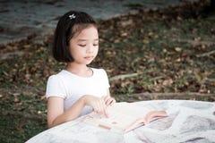 Маленький азиатский ребенок читая книгу стоковые изображения rf