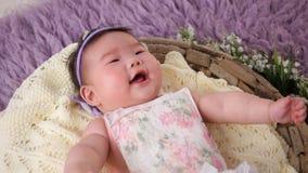 Маленький азиатский ребёнок лежит в шпаргалке корзины в платье и держателе сток-видео