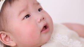 Маленький азиатский ребёнок лежит в шпаргалке корзины в платье и держателе акции видеоматериалы