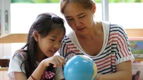 Маленький азиатский студент смотря глобус пока слушающ к учителю акции видеоматериалы