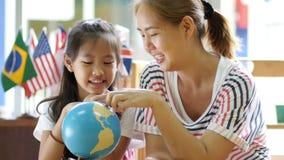 Маленький азиатский студент смотря глобус акции видеоматериалы