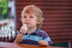 Маленький белокурый мальчик есть желтое мороженое Стоковое Фото