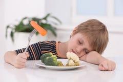 Маленький белокурый мальчик есть на кухне стоковое изображение rf