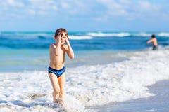 Маленький белокурый мальчик ребенк имея потеху на пляже океана в Флориде стоковая фотография