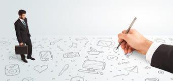 Маленький бизнесмен смотря под рукой нарисованные значки и символы Стоковые Изображения