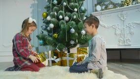Маленький брат и сестра распаковывают подарки Концепция рождества и Нового Года сток-видео