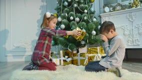 Маленький брат и сестра распаковывают подарки Концепция рождества и Нового Года акции видеоматериалы