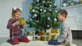 Маленький брат и сестра распаковывают подарки Концепция рождества и Нового Года видеоматериал