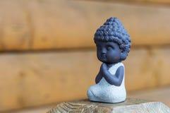 Маленький Будда молит или размышляет на деревянной предпосылке с пустым космосом Молить и раздумье, концепция йоги стоковые изображения rf